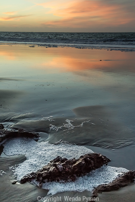 The muted colors of a faded sunset light up the surf with the incoming tide.