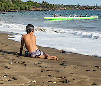 A young local boy watches paddlers take an outrigger canoe out to sea from Hanaka'o'o Beach (or Canoe Beach), Maui. (Note: The boy is model released, the others are not.)
