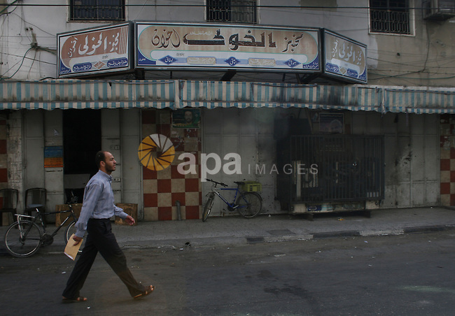 Palestinians pass near closed oven, in Gaza City. Gaza reeled from power outages today as Israel continued to seal off the Hamas-run territory. Bakeries across Gaza City were closing today for lack of electricity to power their ovens.