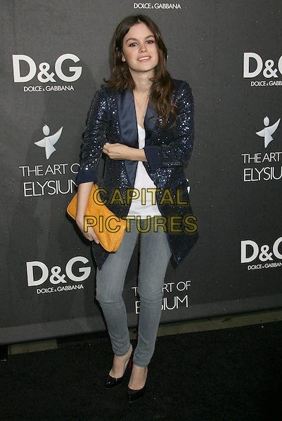 RACHEL BILSON.Boutique Opening Benefiting The Art of Elysium held at the Dolce & Gabana Boutique on Roberston Blvd, Beverly Hills, California, USA..December 15th, 2008.full length blue jacket hand on hip sequins sequined skinny jeans denim orange clutch bag.CAP/ADM/MJ.©Michael Jade/AdMedia/Capital Pictures.
