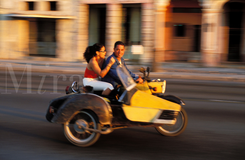 Cuba, Havana. Young couple on a motorcycle  motoring along the Malecon..NO MODEL RELEAS