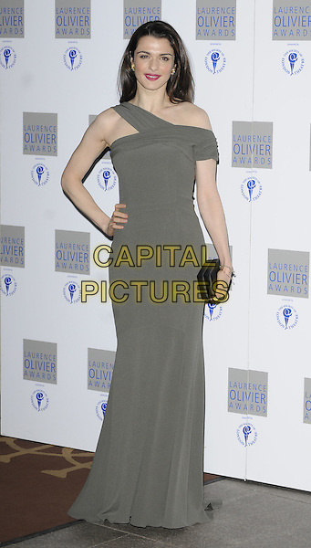 RACHEL WEISZ.The Laurence Olivier Awards 2010, Grosvenor House Hotel, London, England. .21st March 2010. full length grey gray one shoulder off the maxi dress black clutch bag hand on hip.CAP/CAN.©Can Nguyen/Capital Pictures.