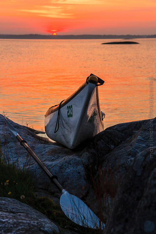 Kajak i solnedgången uppdragen på en klippa i Stockholms skärgård
