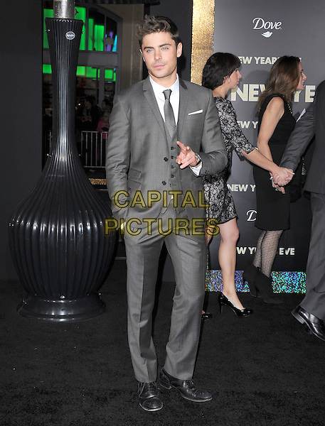 "Zac Efron.The World Premiere of ""New Year's Eve' held at The Grauman's Chinese Theatre in Hollywood, California, USA..December 5th, 2011.full length hand in pocket suit white shirt grey gray tie  v peace sign .CAP/RKE/DVS.©DVS/RockinExposures/Capital Pictures."