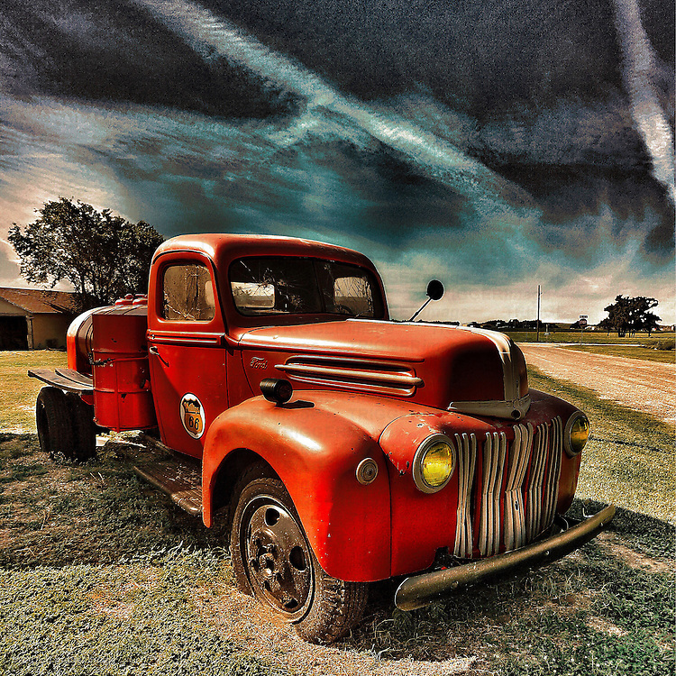 Vintage americana with red pickup under dark sky
