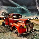 Vintage americana with red pickup under dark sky