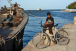 Young boy sits at Diu Jetty, where tourists can take boat rides to see the Diu Fort from the water. The Fortim-do-Mar or Pani Kotha fort is visible behind him. It houses a lighthouse and a chapel for Our Lady of the Sea.