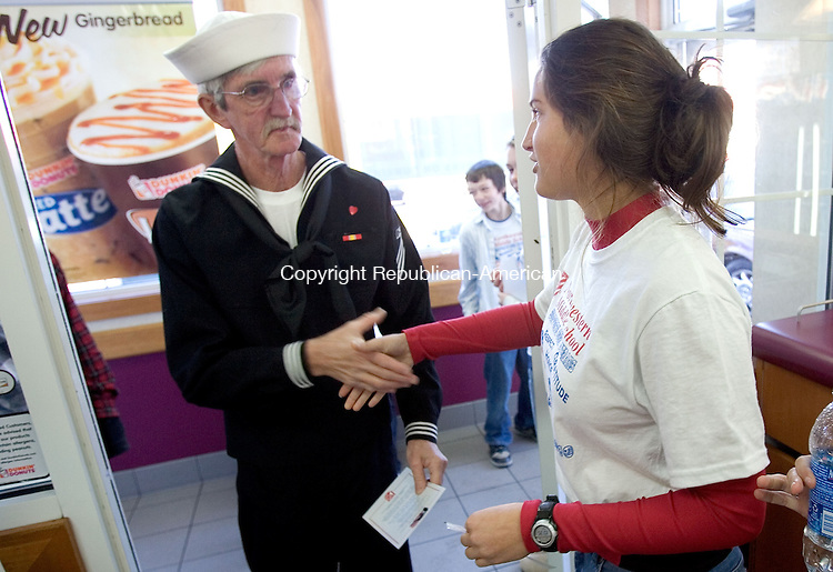 WINSTED, CT. 11 November 2010-111110SV02--From left, Robert Baxter of Winsted is greeted by Kaelin Hester, 13, president of the student council at Northwestern Middle School during a free breakfast for veterans at Dunkin' Donuts in Winsted Thursday.<br /> Steven Valenti Republican-American