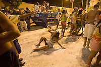 Street Carnival in Brazil - rman in woman's clothes drinks cachaca - community party known as Carnavila at Vila de Ponta Negra quarter in Natal city, Rio Grande do Norte State, northeastern Brazil. Cachaça is the most popular spirit among distilled alcoholic beverage in Brazil.