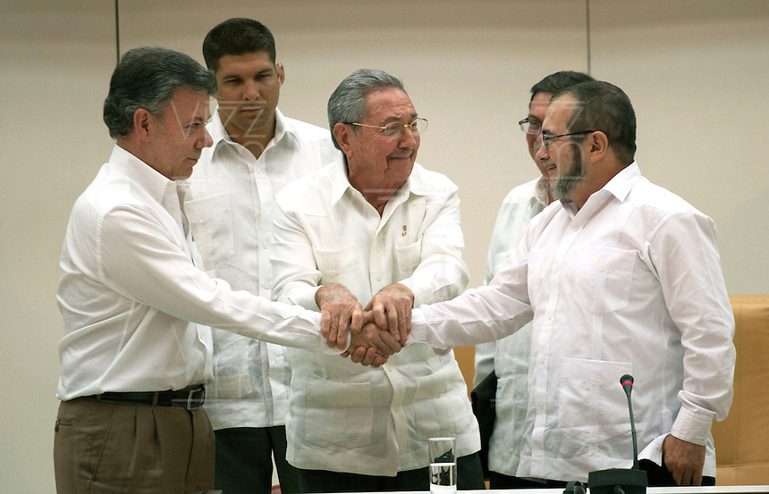 "LA HABANA - COLOMBIA, 23-09-2015 Juan Manuel Santos (Izq) , Presidente de Colombia y Rodrigo Londoño (Der), alias ""Timochenko"", lider máximo de las Farc, se dan un apreton de manos con la intermediación de Raul Castro (C), Presidente de Cuba, hoy 23 de septiembre de 2015, tras el anuncio del acuerdo entre el Gobierno de Colombia y las Farc para poner fin al conflicto armado en Colombia./ Juan Manuel Santos (L), President of Colombia, and Rodrigo Londoño (R), alias ""Timochenko"" shook hands with the intermediation of Raul Castro(C), President of Cuba, today 23 september 2015, after the announcement of the agreetment between Colombia Government and left guerrillas of Farc to give the end of the armed conflict in Colombia. Photo: VizzorImage /  César Carrión - SIG / HANDOUT PICTURE; MANDATORY EDITORIAL USE ONLY/ NO MARKETING, NO SALES"