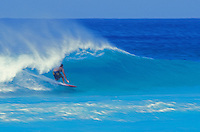 Surfer at speed in the tube on a wave in clear blue water at Ehukai Beach, North Shore of Oahu