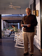 An elderly man reads through the days mail with a smile on his front porch