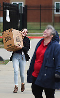 Melissa Ralston, registered dietician, (left) carries a box of cereal cartons to distribute, Friday, March 20, 2020 during a food distribution at Bentonville High School in Bentonville. Check out nwaonline.com/200321Daily/ for today's photo gallery.<br /> (NWA Democrat-Gazette/Charlie Kaijo)<br /> <br /> Dr. Janet Schwanhausser, Bentonville Schools Deputy Superintendent & CFO, partnered with Aramark to set up a drive through food distribution at the campus parking lot. Volunteers and Aramark employees are distributing at five different sites: Bentonville High School, New Life Church in Bella Vista, Centerton Park, Helping Hands Inc. and the Bentonville Library. They are serving packed breakfasts and lunches and will distribute Monday through Friday until school is back in session. They will distribute food between 11am to 12pm at all the sites. They are seeking donations which can be made to Bentonville public schools to support these kinds of initiatives. They are also looking for people to help make snack packs (small snacks for children to eat during the weekend).