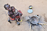 Two children in the Darfur region of Sudan, displaced by government-sponsored ethnic conflict, sit in a displaced persons camp near a fire where there's no food to be cooked.