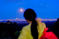 EAGLE ROCK, NJ - JUNE 09: A woman takes a look of the Strawberry Moon as it rises over lower Manhattan on June 06, 2017 in Montclair, New Jersey. Photo by VIEWpress/Eduardo MunozAlvarez