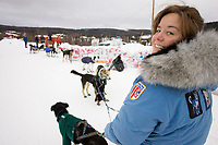 Volunteer checker Stacy Merrill from Anchorage holds Gerald Sousa's lead dogs at Ruby on Saturday morning while he checks in during Iditarod 2008