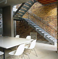 An open metal staircase runs up the side of a revealed brick wall from the dining/kitchen area
