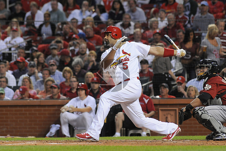 18 May 2011                             St. Louis Cardinals first baseman Albert Pujols (5) follows through while batting.  Astros catcher is Humberto Quintero. The St. Louis Cardinals defeated the Houston Astros 5-1 on Wednesday May 18, 2011 in the first game of a two-game series at Busch Stadium in downtown St. Louis.