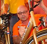 Engeland, London, 26 juli 2012.Olympische Spelen London.Opening Holland Heineken House.Maurits Hendriks van het  NOC*NSF zet zijn hantekening op een gouden fiets die voor de Nederlandse Olympische sporters beschilbaar is gesteld