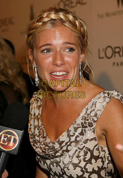 SIENNA MILLER.Attending The Weinstein Company's 2007 Golden Globes After Party held at Trader Vics at The Beverly Hilton Hotel, Beverly Hills, California, USA, 15 January 2007..portrait headshot gold and white dress patterned printed  plait braid in hair microphone interview funny face.CAP/ADM/RE.©Russ Elliot/AdMedia/Capital Pictures.