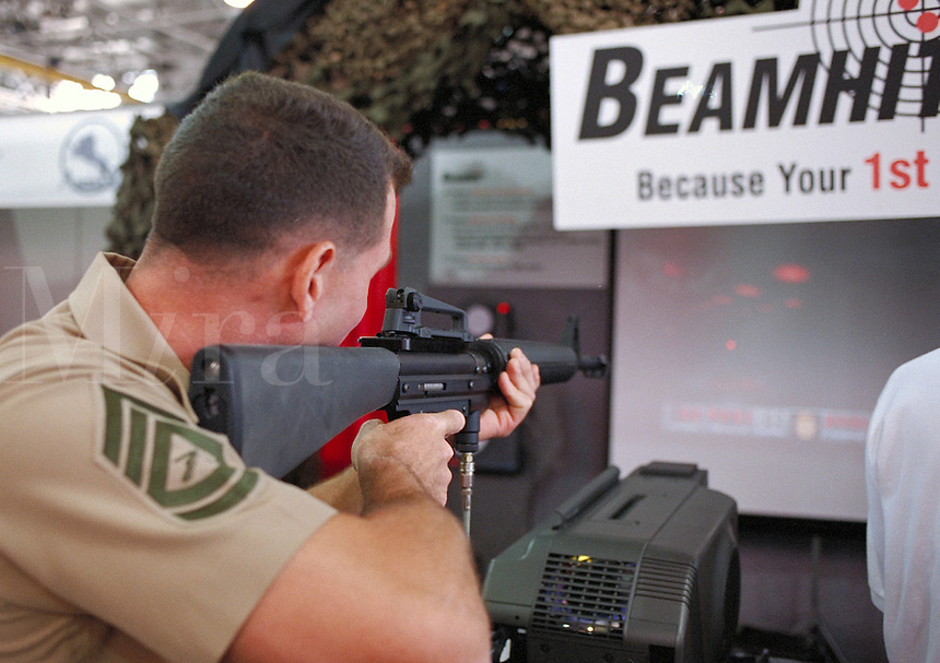 "Modern Marine"""" military arms trade show at Quantico, Virginia. A marine tries out a computerized M-16 combat firing range simulator.. Quantico Virginia."