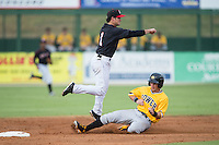 Kannapolis Intimidators shortstop Eddy Alvarez (1) makes a throw to first base as Jeff Roy (5) of the West Virginia Power slides into second base at Intimidators Stadium on July 2, 2015 in Kannapolis, North Carolina.  The Power defeated the Intimidators 5-1.  (Brian Westerholt/Four Seam Images)