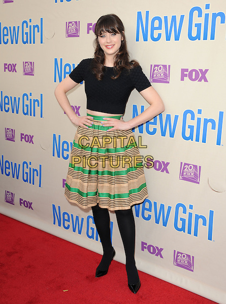 "Zooey Deschanel.""New Girl"" Screening and Q&A held at the Academy of Television Arts & Sciences..April 30th, 2013.full length black top beige gold green stripe skirt hands on hips tights                                            .CAP/RKE/DVS.©DVS/RockinExposures/Capital Pictures."