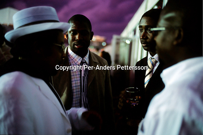DURBAN, SOUTH AFRICA - July 3: Black yuppies talk at a black empowerment reception during the yearly Durban July horse race on July 3, 2004 in Durban in Natal Province, South Africa. Durban July is the biggest horse race in Africa and an important social event, where South Africa's celebrities dress up and watch the races. Durban is a popular tourist destination situated on Indian Ocean.  .(Photo: Per-Anders Pettersson/Getty Images).....