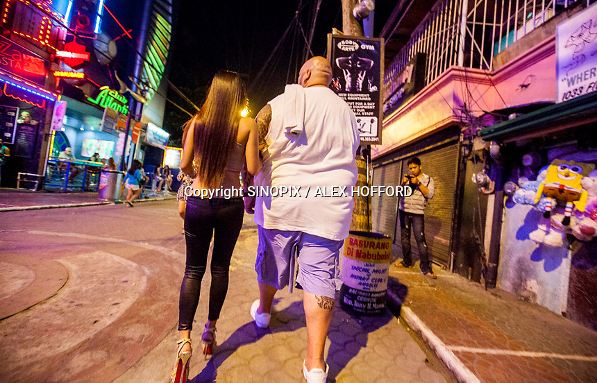 A man is seen with a prostitute on Fields Avenue, the main strip of bars offering cheap prostitutes that runs through Angeles City, Republic of the Philippines, 08 November 2014. The 'sin city', which sprung up on the fringes of a US Air Force base during the Vietnam war, has a reputation for cheap sex, and was a favourite destination for alleged murderer Rurik Jutting, who used to fly to Angeles City from Hong Kong for debauched weekends. The British banker is currently on remand at a secure facility in Hong Kong for allegedly murdering two Indonesian prostitutes in his flat whilst high on alcohol and cocaine.
