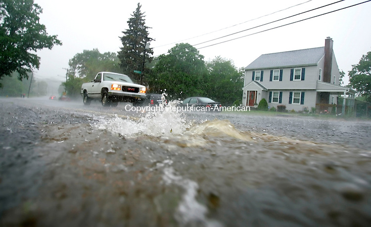 WATERBURY, CT. 02 June 2006-060206SV15--Cars pass by over flowing storm drains on Chase Parkway during a heavy rain storm in Waterbury Friday.<br /> Steven Valenti Republican-American