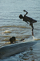 A boy is jumping from a boat Tonle Sap Lake, Cambodia