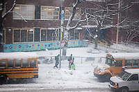 "Students pass snow covered school buses as they enter Public School 33 in the Chelsea neighborhood of New York on Thursday, February 13, 2014. The NYC Dept. of Education has not declared a ""snow day"" during this winter storm which is expected to dump at least six inches onto the metropolitan area.  (© Richard B. Levine)"
