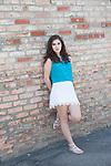 Portrait of a teenage girl with dark brown hair agaiost a brick wall