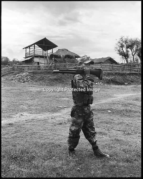 25 year old Lance Corporal Assampad Dimasa poses for a portrait with a Lethode bomb launcher at the Basabari camp of the ceasefire terrorist group Dima Halim Daoga (DHD) in Mibang in North Cachar hills of Assam, India.