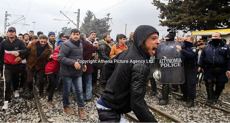 Pictured: Refugees clash with Greek police Monday 29 February 2016<br /> Re: A crowd of migrants has burst through a barbed-wire fence on the FYRO Macedonia-Greece border using a steel pole as a battering ram.<br /> TV footage showed migrants pushing against the fence at Idomeni, ripping away barbed wire, as FYRO Macedonian police let off tear gas to force them away.<br /> A section of fence was smashed open with the battering ram. It is not clear how many migrants got through.<br /> Many of those trying to reach northern Europe are Syrian and Iraqi refugees.<br /> About 6,500 people are stuck on the Greek side of the border, as FYRO Macedonia is letting very few in. Many have been camping in squalid conditions for a week or more, with little food or medical help.