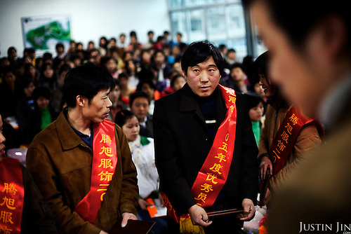"""Model garment workers are awarded with red banners in Wenzhou city, China, as the country winds down for Chinese New Year. .This picture is part of a photo and text story on blue jeans production in China by Justin Jin. .China, the """"factory of the world"""", is now also the major producer for blue jeans. To meet production demand, thousands of workers sweat through the night scrubbing, spraying and tearing trousers to create their rugged look. .At dawn, workers bundle the garment off to another factory for packaging and shipping around the world..The workers are among the 200 million migrant labourers criss-crossing China.looking for a better life, at the same time building their country into a.mighty industrial power."""