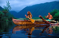 Couple in thier outrigger canoe heading out to the ocean in Waipio Valley on the Big Island of Hawaii.