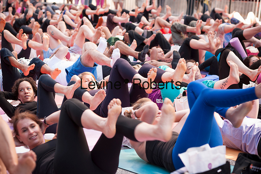 """Thousands of yoga practitioners pack Times Square in New York to participate in a Power Yoga class on the first day of summer, Saturday, June 21, 2014. The 12th annual Solstice in Times Square, """"Mind Over Madness"""",  stretches the yogis' ability to block out the noise and the visual clutter that surround them in the Crossroads of the World. (© Richard B. Levine)"""