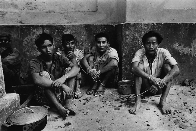 Four suspected members of the Khmer Rouge awaiting interrogation, Cambodia 1975