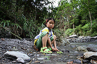 A young girl plays in a stream in the forested mountains of Pingwu County in Sichuan Province, south-west China.