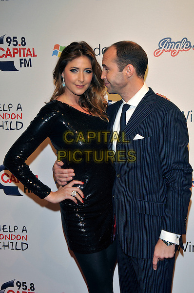 LISA SNOWDON & JOHNNY VAUGHAN.95.8 Capital FM Jingle Bell Ball at 02 Arena Greenwich, London, England 5th December 2009.half length black sequins sequined dress one shoulder hand ring on hip blue suit jacket pinstripe profile arm around waist .CAP/PL.©Phil Loftus/Capital Pictures.