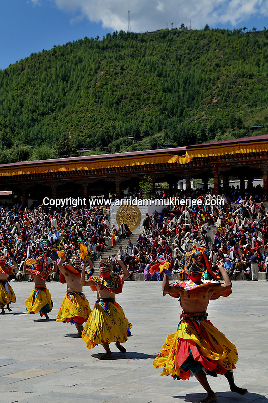 "Monks perfom during annual Thimpu Tshechu. The Tshechu is a festival honouring Guru Padmasambhava, ""one who was born from a lotus flower."" This Indian saint contributed enormously to the diffusion of Tantric Buddhism in the Himalayan regions of Tibet, Nepal, Bhutan etc. around 800 AD. He is the founder of the Nyingmapa, the ""old school"" of Lamaism which still has numerous followers. The biography of Guru is highlighted by 12 episodes of the model of the Buddha Shakyamuni's life. Each episode is commemorated around the year on the 10th day of the month by ""the Tschechu"". The dates and the duration of the festivals vary from one district to another but they always take place on or around the 10th day of the month according to the Bhutanese calendar. During Tshechus, the dances are performed by monks as well as by laymen. The Tshechu is a religious festival and by attending it, it is believed one gains merits. It is also a yearly social gathering where the people, dressed in all their finery, come together to rejoice. Arindam Mukherjee."