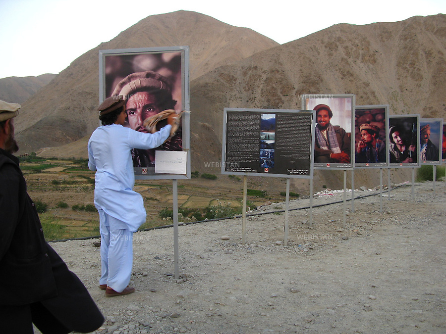 AFGHANISTAN - VALLEE DU PANJSHIR - 14 aout 2009 :.Exposition organisee par Reza sur le site du tombeau du commandant Massoud. Plus de cinquante photographies representant Massoud et ses hommes lors des guerres contre les russes puis les talibans etaient exposees autour des vestiges de tanks et de pieces d'artillerie russes pris par les moudjahidin lors de leurs assauts ..Delazad Deghati nettoyant une photographie du Commandant Massoud. ..AFGHANISTAN - PANJSHIR VALLEY - August 14th, 2009: Exhibition organized by Reza at the site of Commander Massoud's tomb..More than fifty photographs of Massoud and his men taken during their fights against the Russians and the Taliban were exhibited amongst the vestiges of Soviet tanks and artillery seized by the mujahideen during their battles..Delazad Deghati cleaning a photograph of Commander Massoud.