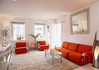 The living room is furnished in retro style with modular pieces upholstered in orange fabric