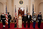 Washington, DC - November 24, 2009 -- United States President Barack Obama, third from right, and U.S. First Lady Michele Obama, fifth from the right, pose for a photograph in the Crosshall of the White House with Manmohan Singh, India's prime minister, fourth from the right, and his wife Gursharan Kaur, sixth from the right,  in Washington, D.C., U.S., on Tuesday, November 24, 2009. Obama welcomed India's role as a rising and responsible global power, saying the U.S. will follow through on a civilian nuclear agreement and work to expand trade and investment ties with the world's largest democracy. .Credit: Andrew Harrer - Pool via CNP