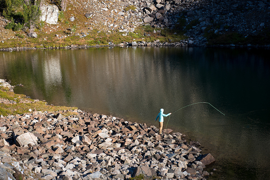 Christine Marozick, of Bozeman, Montana, fishes as dawn breaks on Twin Lake in the Tobacco Root Mountains near Twin Bridges, Montana.