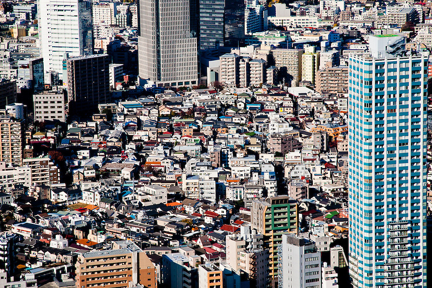 Tokyo`s cramped & varied housing seen from an aerial view point. Old housing surrounded by newer high rises.