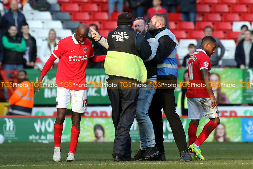 A Charlton protestor is escorted off the pitch by a couple of stewards during Charlton Athletic vs Middlesbrough, Sky Bet Championship Football at The Valley on 13th March 2016