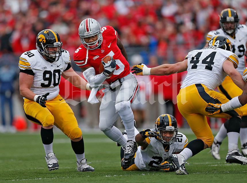 Ohio State Buckeyes quarterback Braxton Miller (5) slices his way through Iowa defenders Iowa Hawkeyes defensive lineman Louis Trinca-Pasat (90), Iowa Hawkeyes linebacker Christian Kirksey (20) and Iowa Hawkeyes linebacker James Morris (44) in the first half at Ohio Stadium on October 19, 2013.  (Chris Russell/Dispatch Photo)
