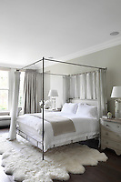 A calm bedroom furnished in neutral tones with matching bedside storage and lamps